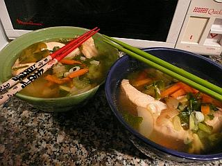 Two Bowls Of Poached Salmon And Noodle Soup.